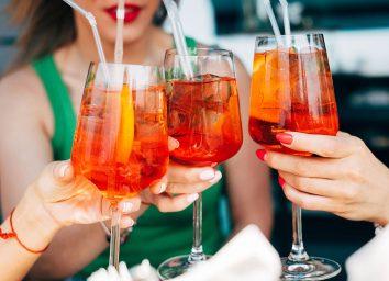 women holding aperol spritz cocktails