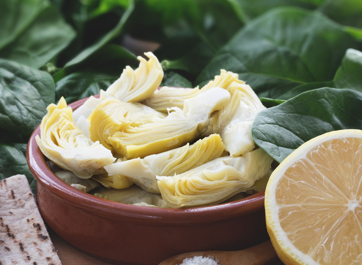 Artichoke hearts in bowl with half lemon
