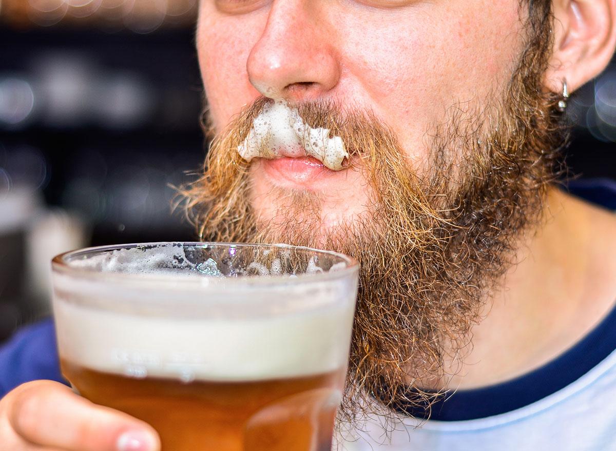 beer foam stuck in mans facial hair on upper lip