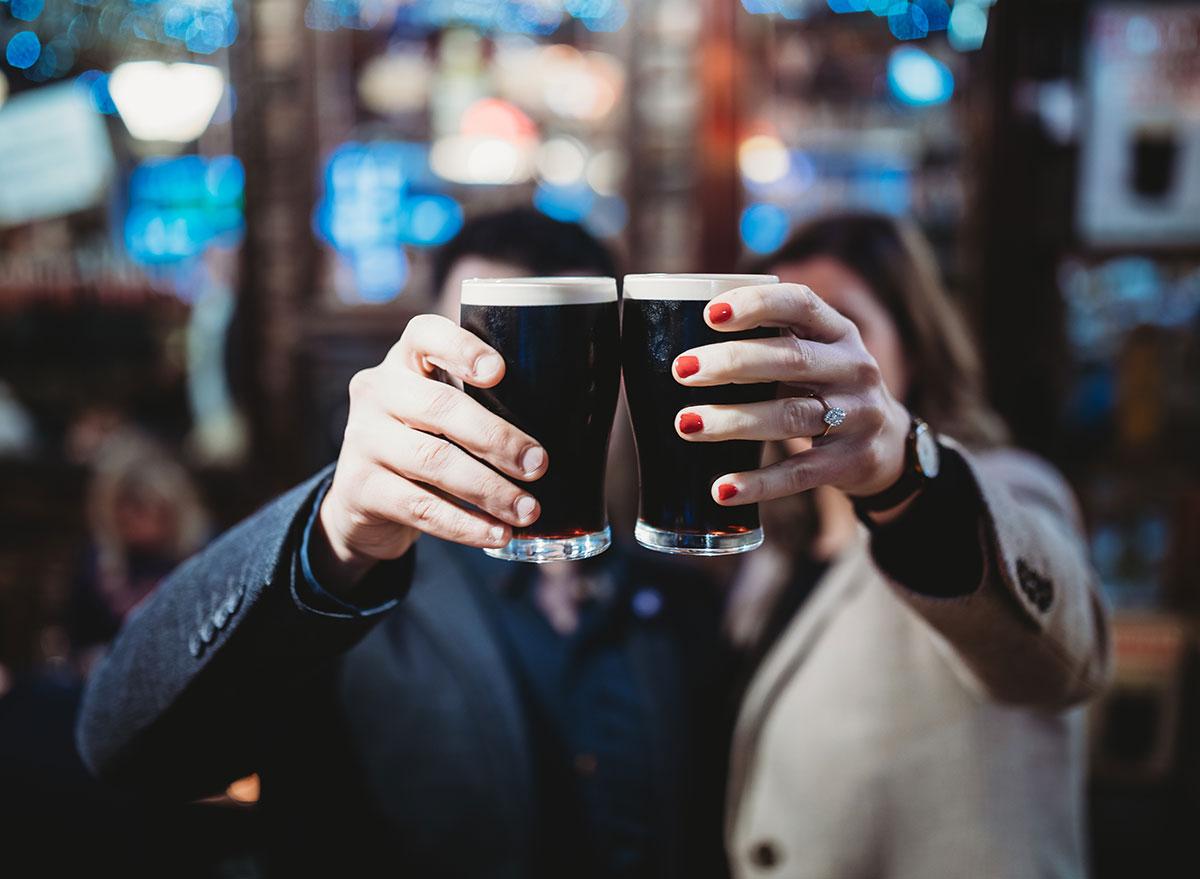 man and woman holding up glasses of dark beer guinness