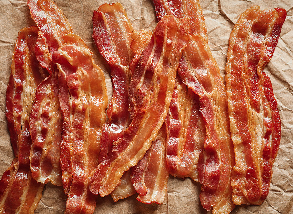 strips of cooked bacon lying on brown parchment paper