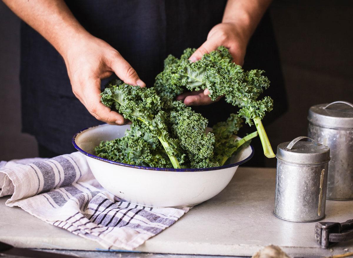Kale dark leafy greens hand massaged in bowl - calcium rich foods