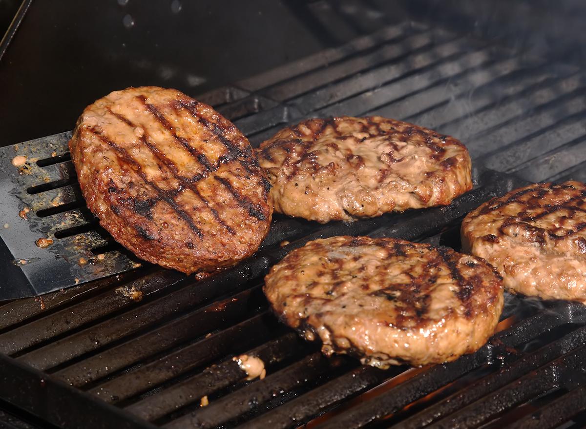 spatula flipping burger patty on open grill
