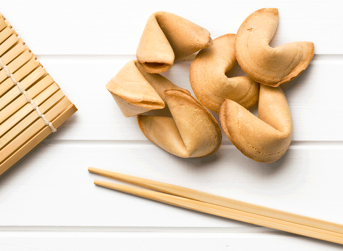 fortune cookies next to bamboo chopsticks and place mat