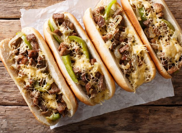 four philly cheesesteaks with cheese and peppers