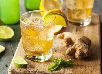 glass of ginger ale on wooden cutting board with ginger root lemon lime and mint leaves