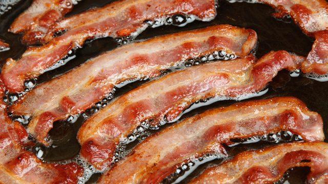 greasy bacon frying in oil in a pan