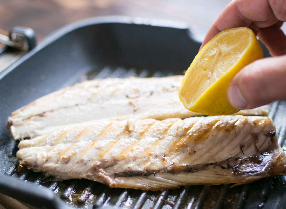 Grilled mackerel on grill pan squeezing lemon juice by hand