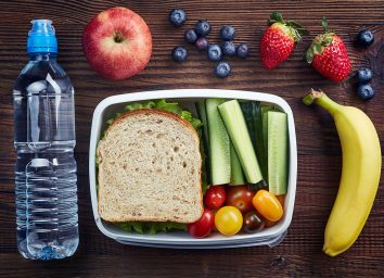 sandwich in a container with cucumber sticks heirloom tomatoes surrounded by blueberries strawberries an apple a banana and a plastic water bottle