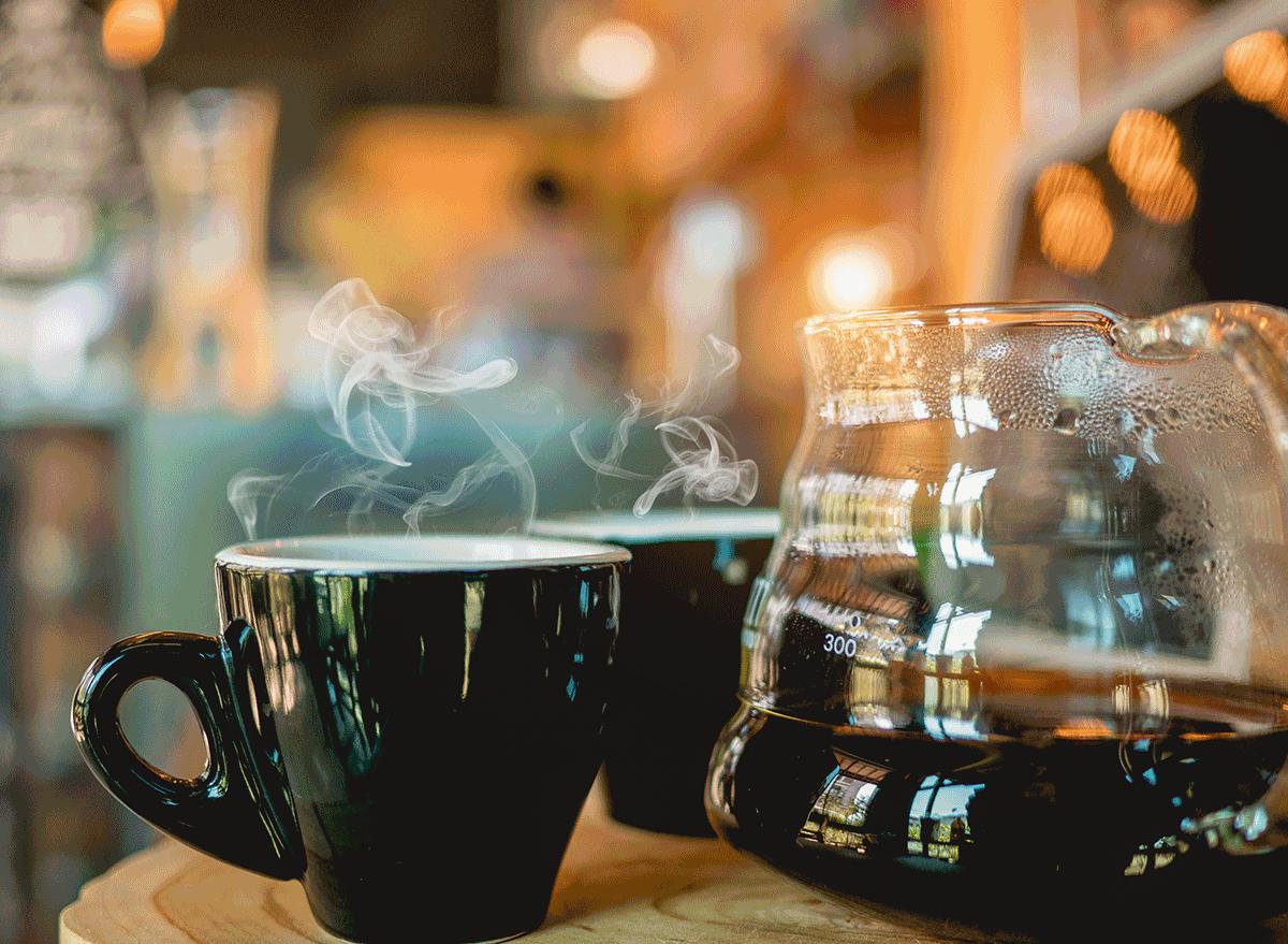 steaming hot coffee mug next to pot
