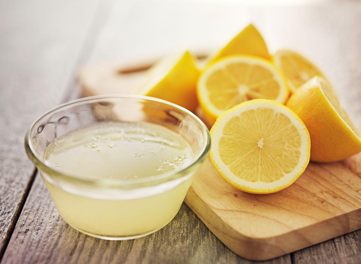 lemon juice in bowl next to sliced lemons