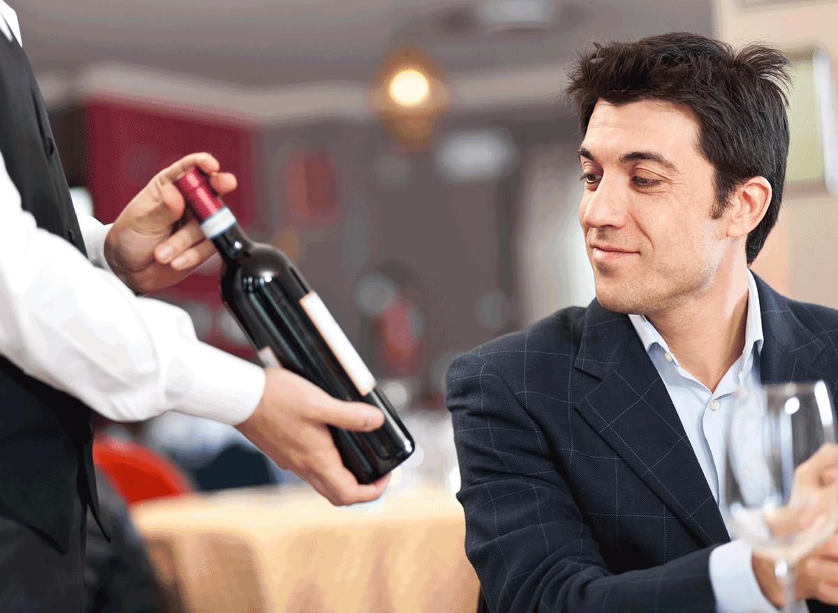man thinking of buying wine