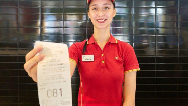 mcdonalds worker handing receipt