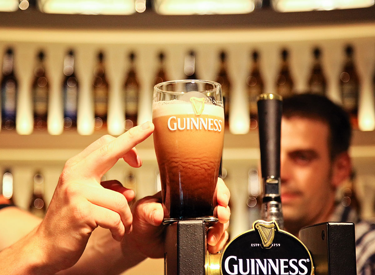 poured guinness in glass with red tint