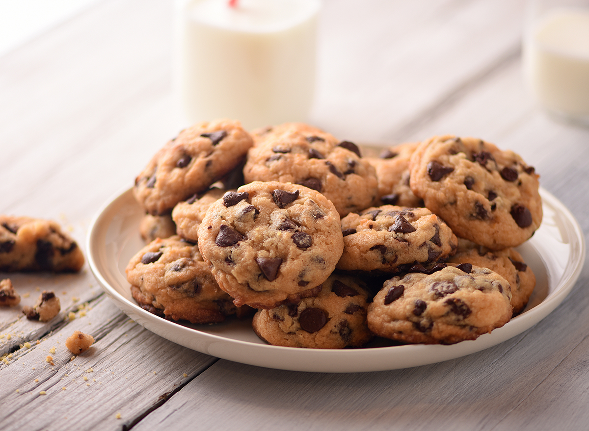 chocolate chip cookies on a plate with two cups of milk in the background