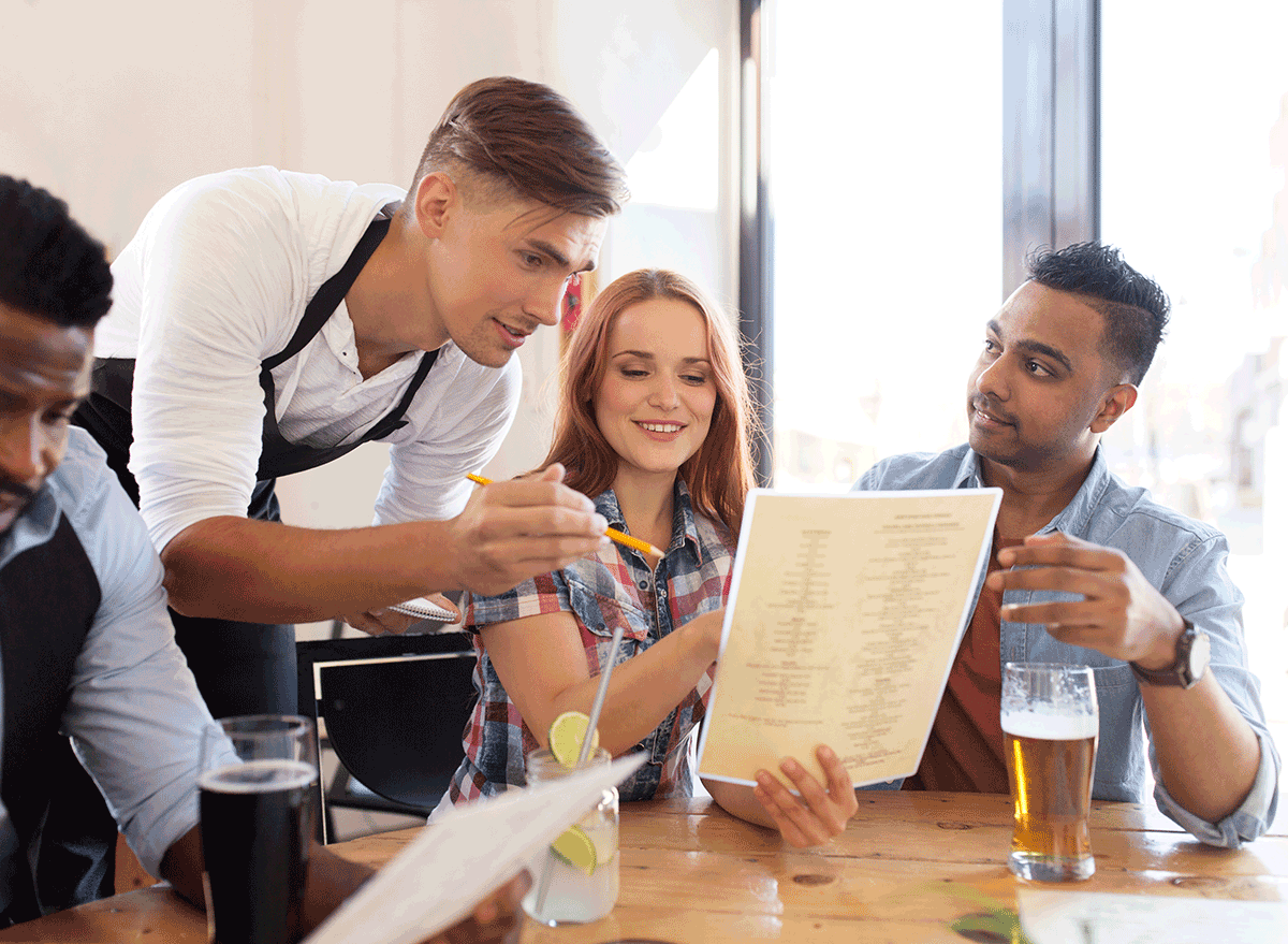 server making a suggestion to couple about menu