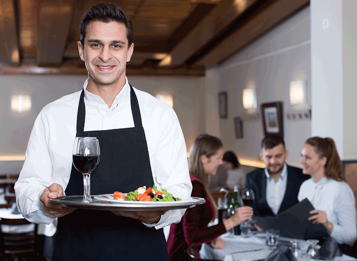 server with drinks and salad on tray standing by table