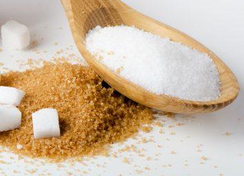 white sugar in wooden spoon resting on brown sugar