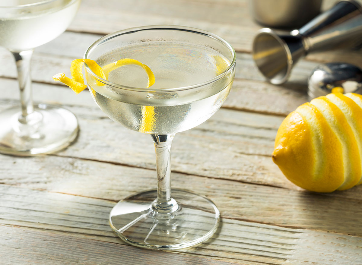 the vesper cocktail in tall glass with lemon peel garnish