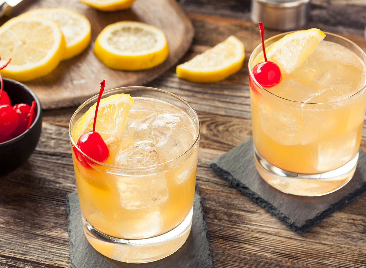 whiskey sour cocktails in glass with cherry lemon garnish