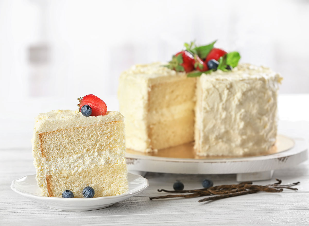 white cake slice out of cake with fruit on top of frosting
