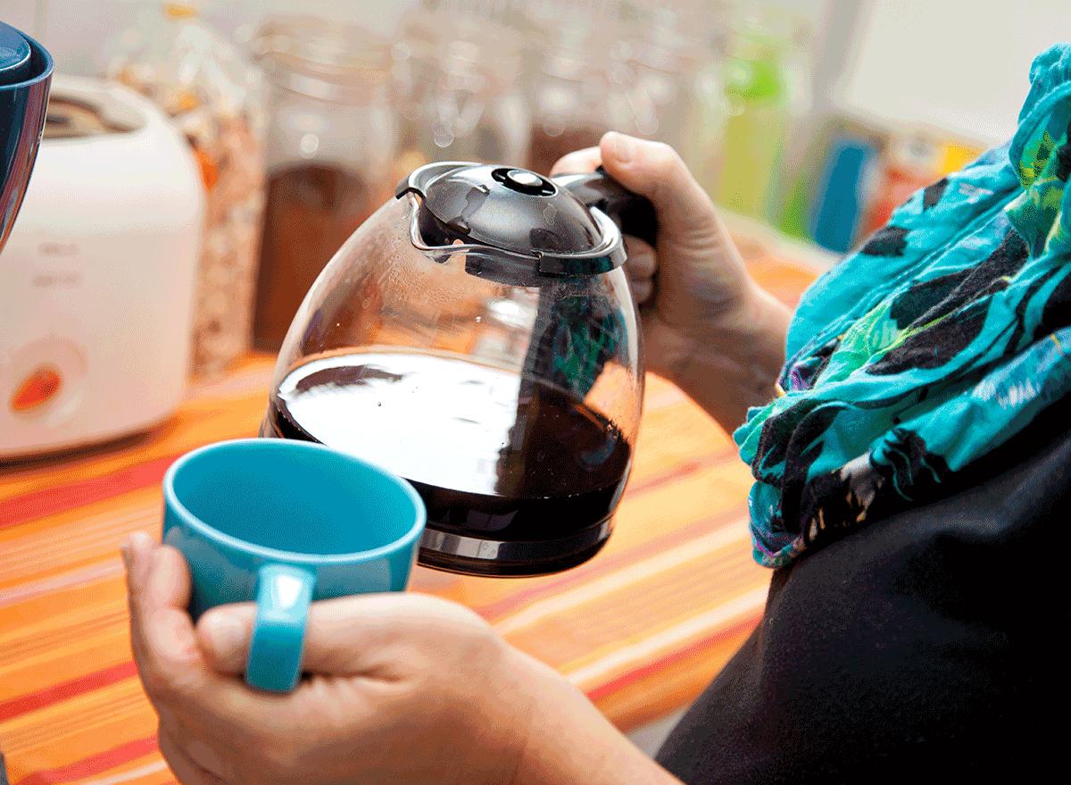 woman holding coffee pot and mug