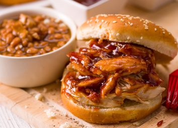 BBQ pork sandwich with a cup of beans