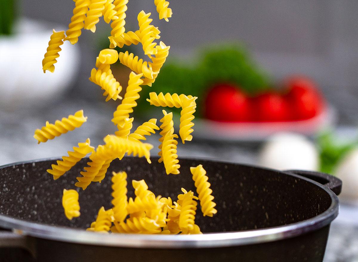 adding pasta to cooking pot