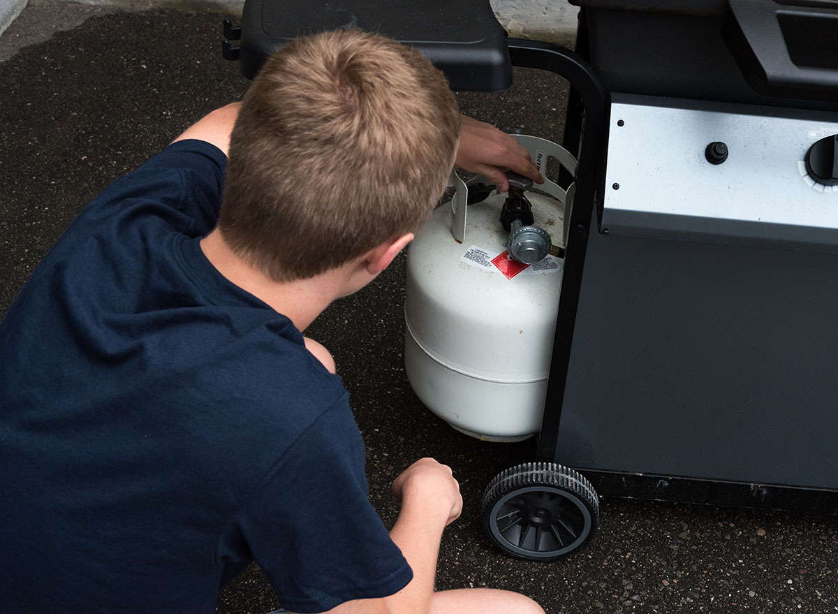 boy touching propane tank for grill