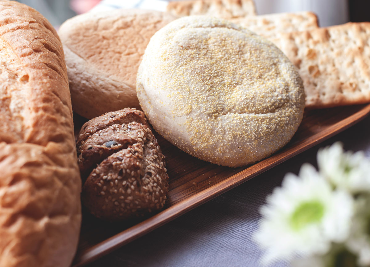 Loaf of bread seedy grain roll english muffin whole wheat crackers on wooden tray