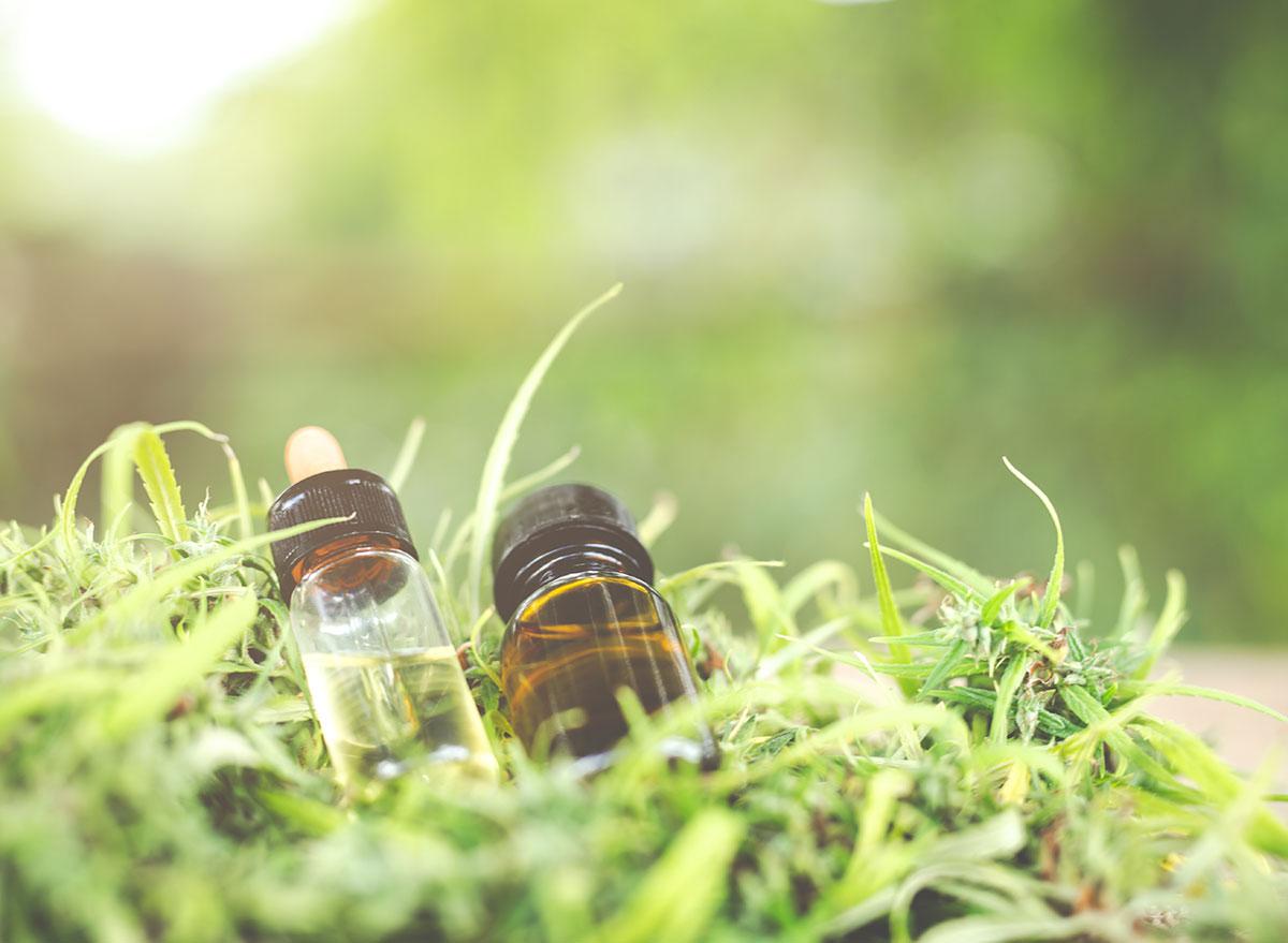 cbd oil on pile of marijuana leaves