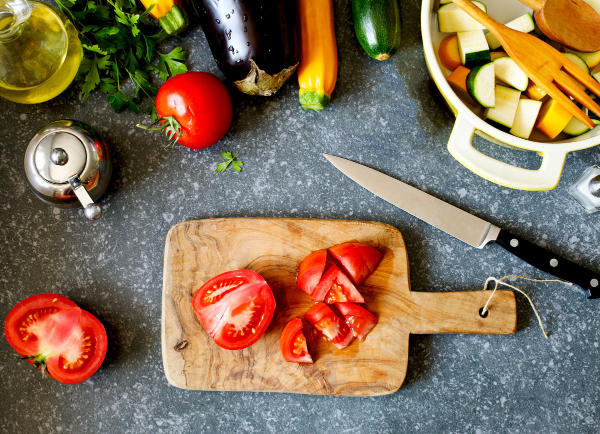 Low fodmap meal prep chopped tomatoes wooden cutting board zucchini in bowl