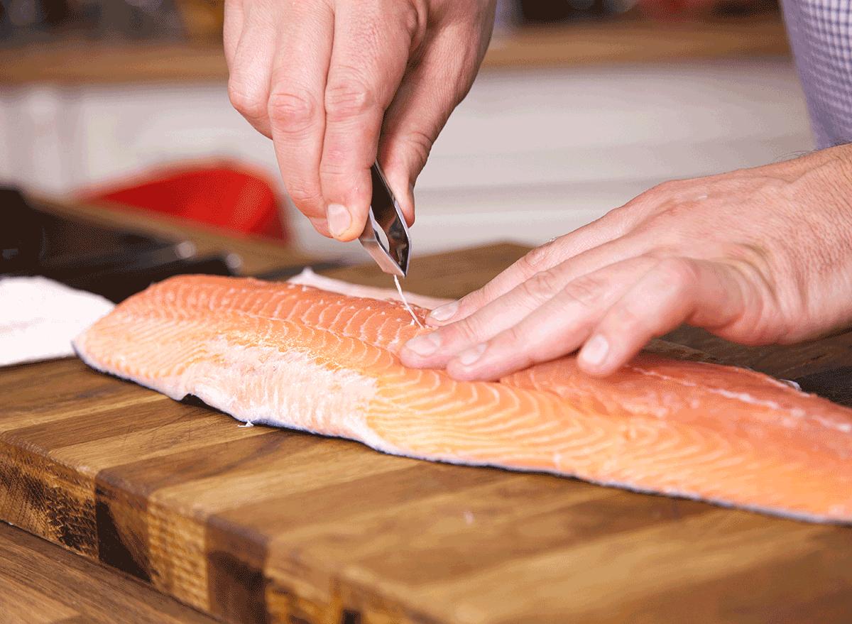 man using tool to debone salmon skin