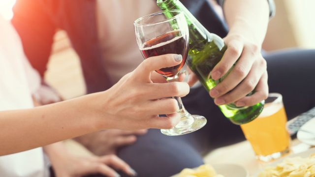 clinking wine glass and beer bottle