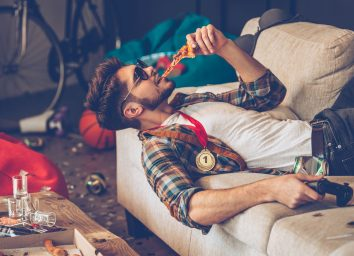 drunk man eating pizza on couch in messy room