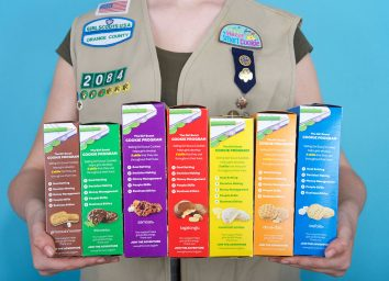 girl scout holding boxes of cookies