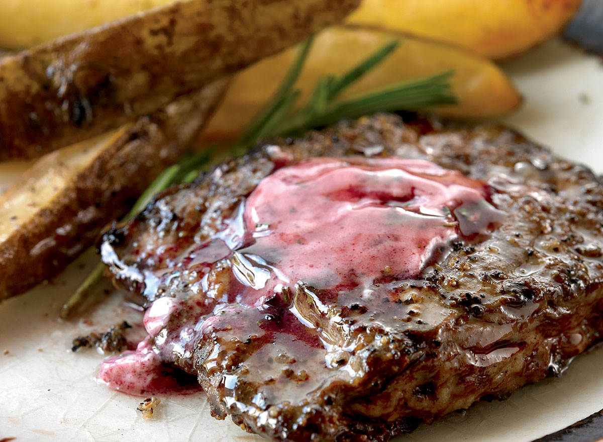 grilled steak topped with red wine butter next to steak fries
