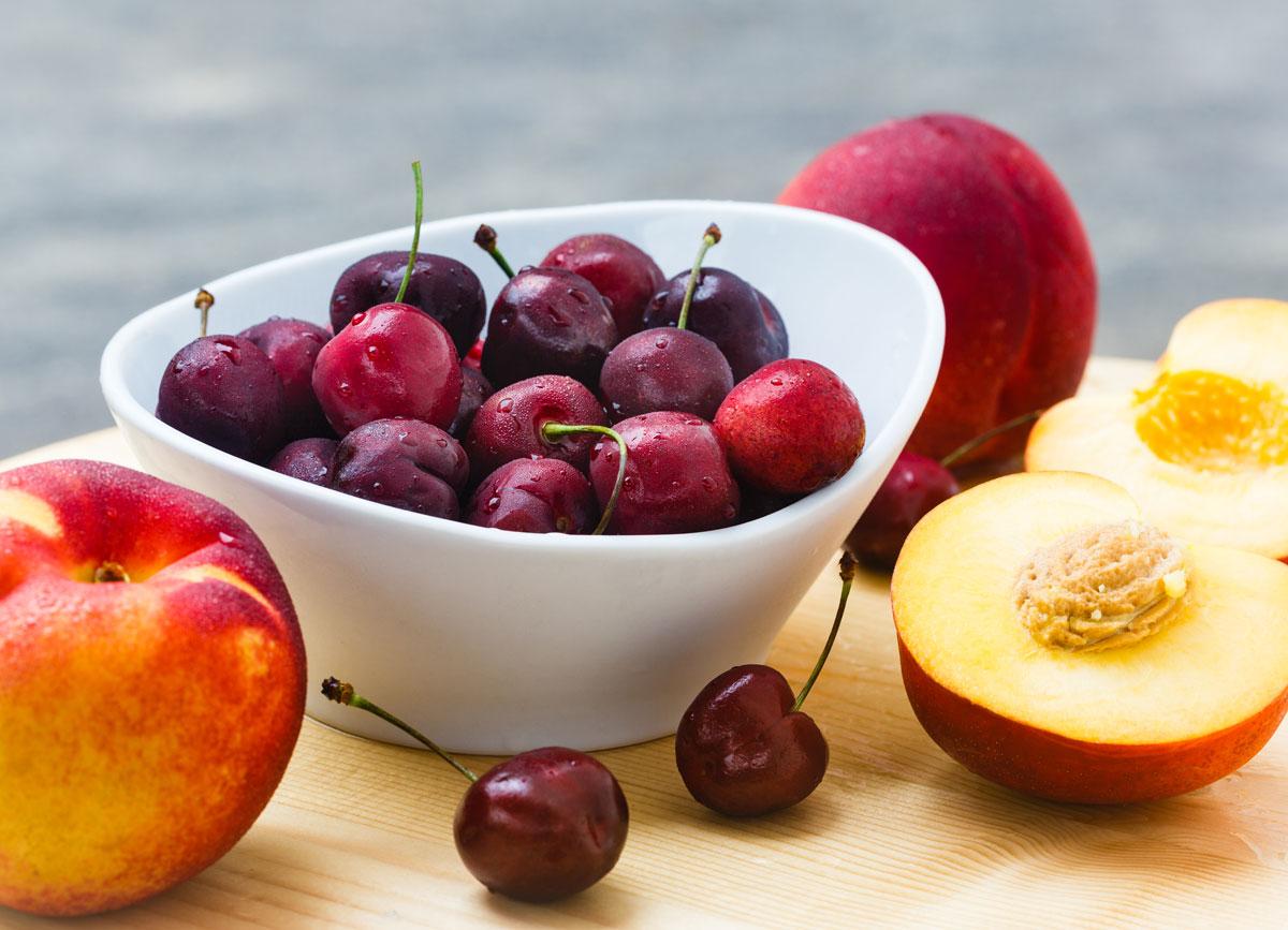 High fodmap fruits cherries peaches on wooden cutting board