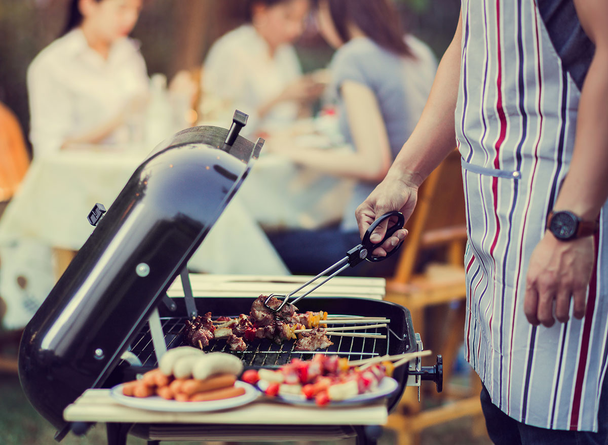 man barbecuing for family