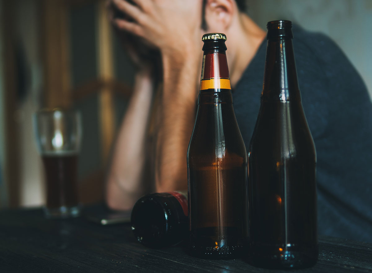 man holding head at bar with beers - how does alcohol affect the brain