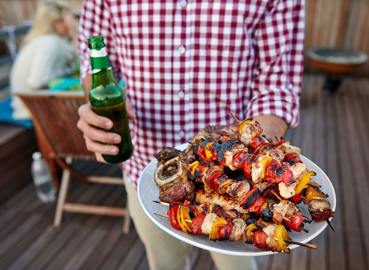 man holding plate of grilled food with beer