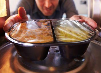 man microwaving frozen meal