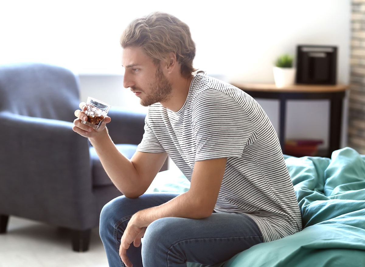 man sitting on bed with alcohol glass - how does alcohol affect the brain