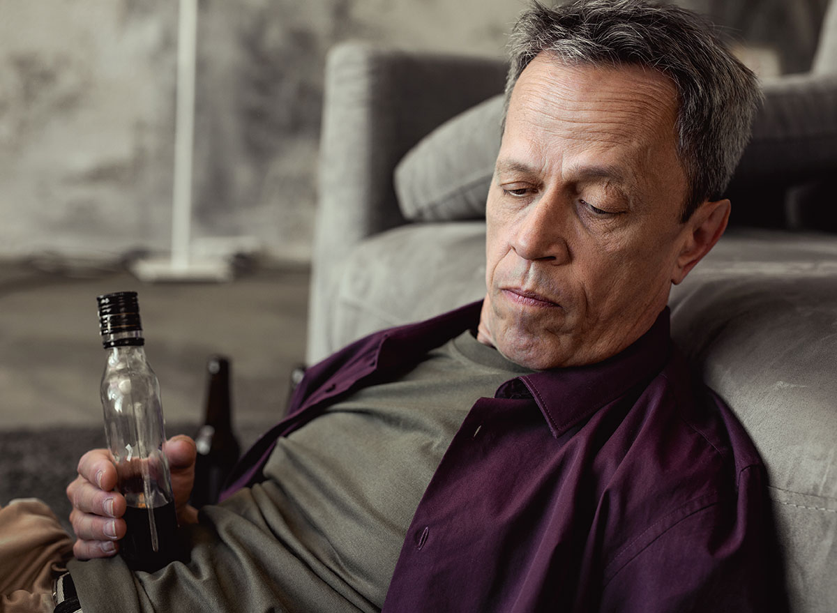 man staring with liquor bottle in hand - how does alcohol affect the brain