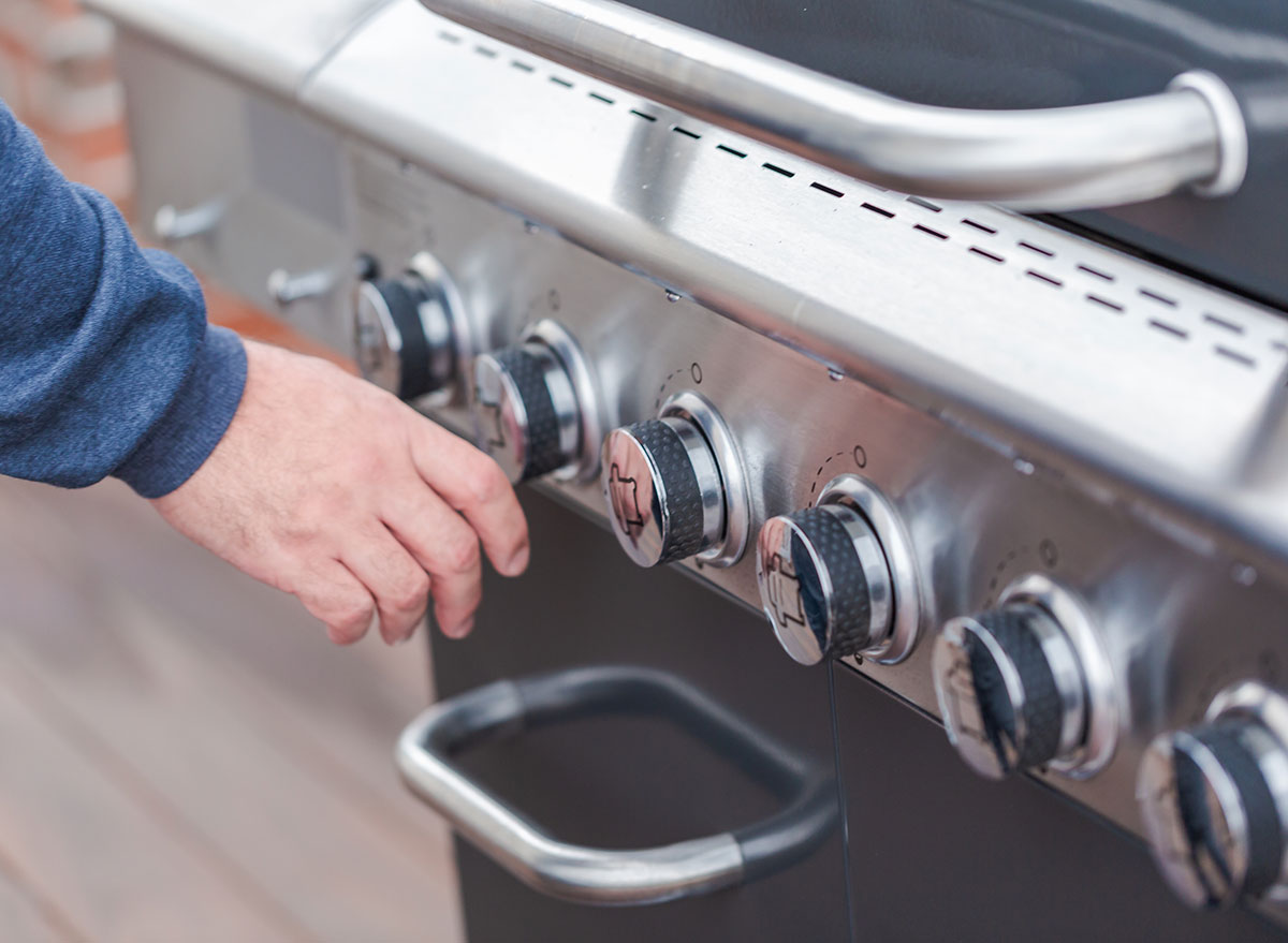 man touching grill knobs
