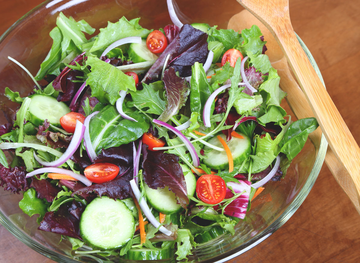 mixed green salad in glass bowl no dressing