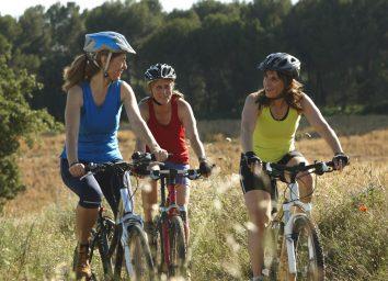 older women biking outside exercising