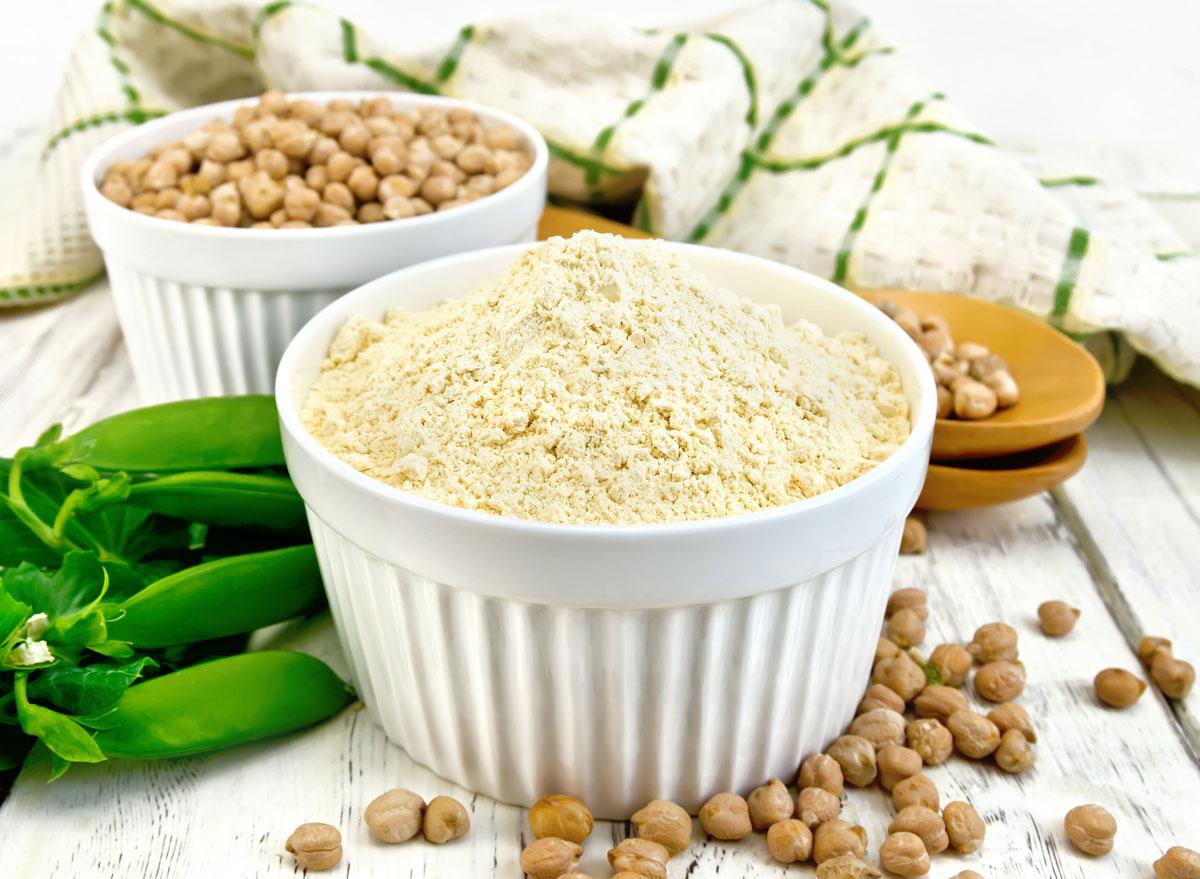 Pea protein powder in white ramekin next to whole pea pod