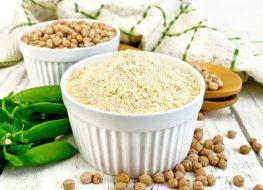 Vegan pea protein powder in white ramekin next to whole pea pod