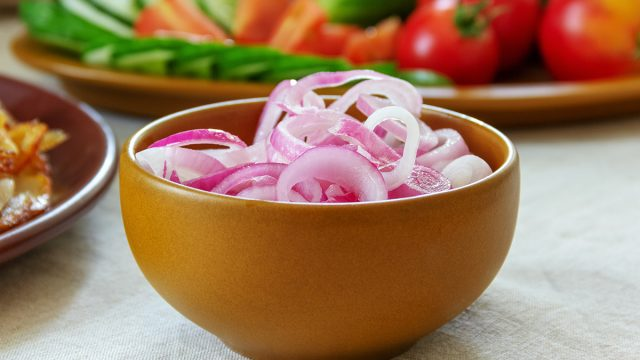 pickled red onion in a light brown ceramic bowl